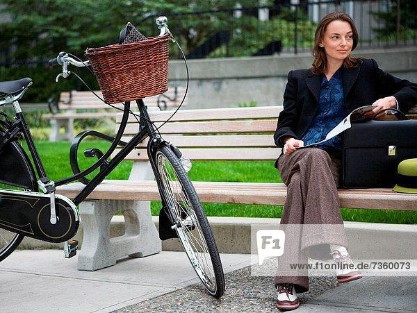 Junge Frau sitzt auf einer Bank in einem park