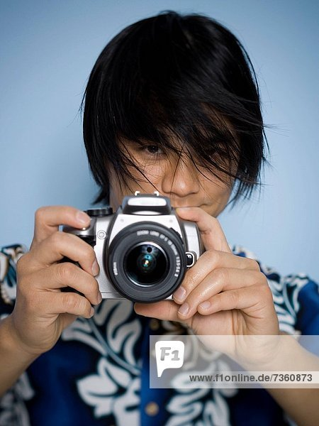 Portrait of a young man taking a photograph with a camera