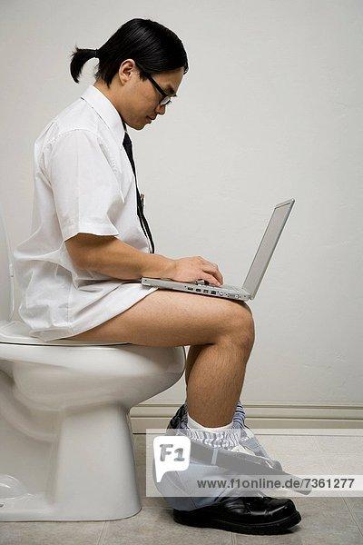 Profil  Profile  sitzend  benutzen  Mann  Notebook  jung  Toilette