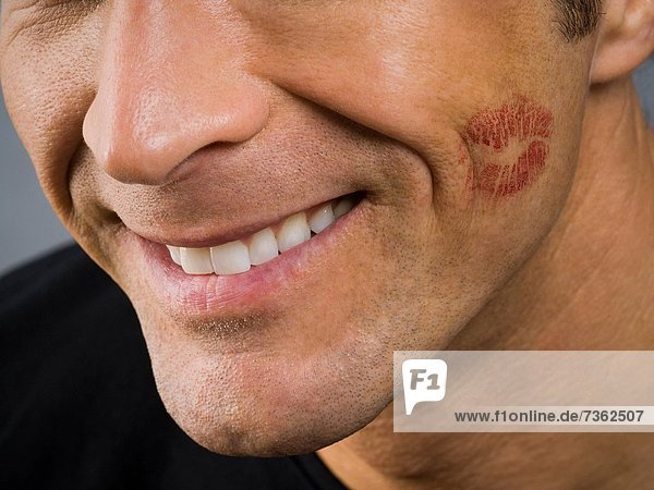 Close_up of a mature man with lipstick on his cheek