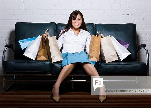 Portrait of a young woman sitting on a couch with shopping bags