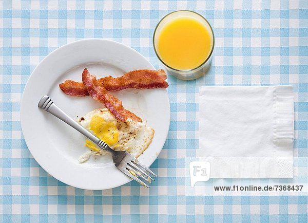 Bacon and eggs with orange juice fork and napkin Bacon and eggs with orange juice fork and napkin