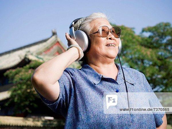 Außenaufnahme  Frau  lächeln  Kopfhörer  reifer Erwachsene  reife Erwachsene  freie Natur