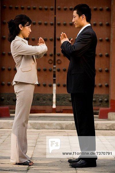 Außenaufnahme  Mann  Geschäftsfrau  grüßen  in die Augen sehen  ansehen  Angesicht zu Angesicht  gegenüber  freie Natur