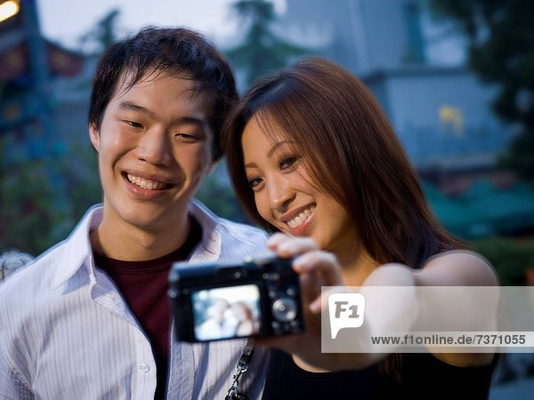 Couple embracing and smiling outdoors with camera