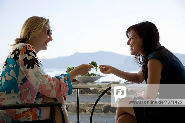 Two women eating salad outdoors and smiling with rock formation in background