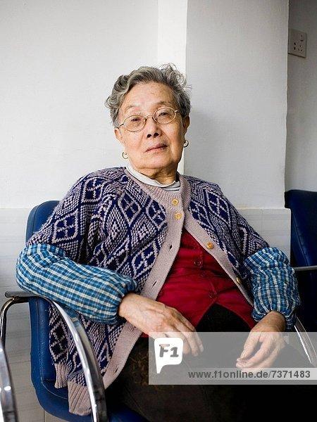 sitzend  Frau  Brille  Stuhl  reifer Erwachsene  reife Erwachsene  blau