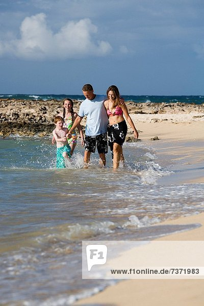 Couple with boy and girl walking in water on sandy beach