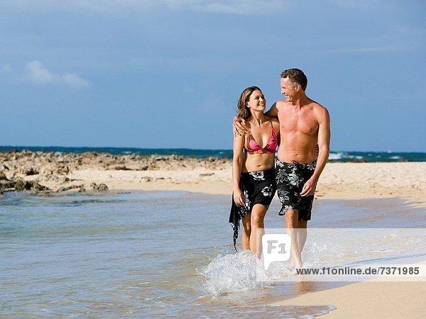 Man and woman walking on shoreline embracing