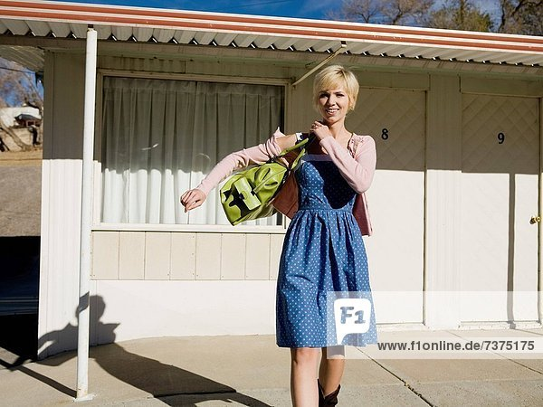 woman in front of a motel room.