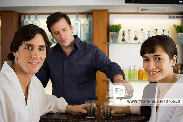 Bartender serving a young couple at a bar counter