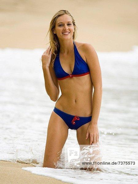 Portrait einer jungen Frau kniend am Strand
