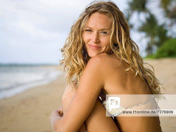 Portrait einer jungen Frau sitzend am Strand
