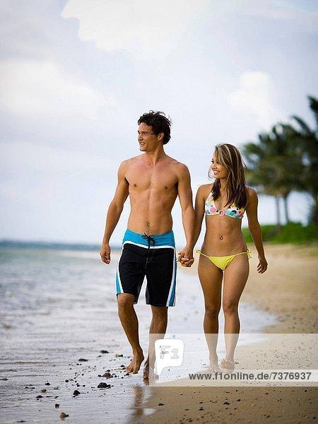 Junges paar hält hände und Wandern am Strand