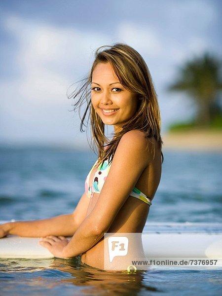 Portrait of a junge Frau hält ein Surfbrett