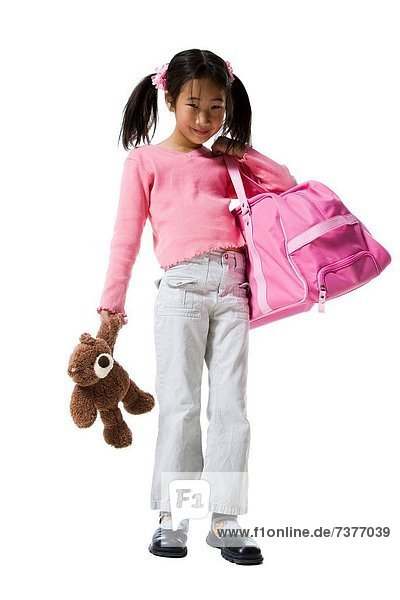 Portrait of a girl holding a teddy bear and a schoolbag