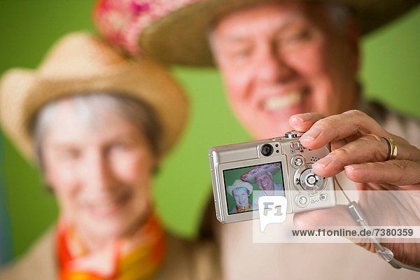 Close_up of an elderly couple taking a photograph of themselves