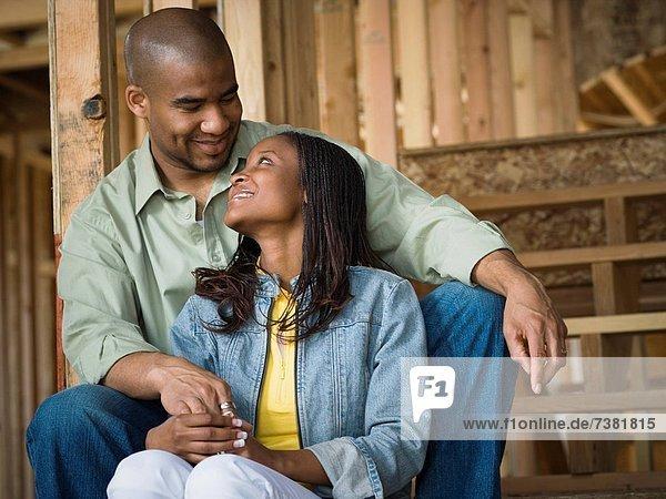 Porträt eines jungen Paares sitzen und lächelnd