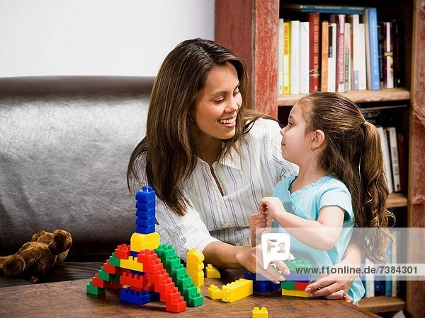 Mother and young daughter playing with building blocks