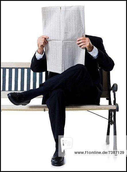 Businessman sitting on bench reading newspaper