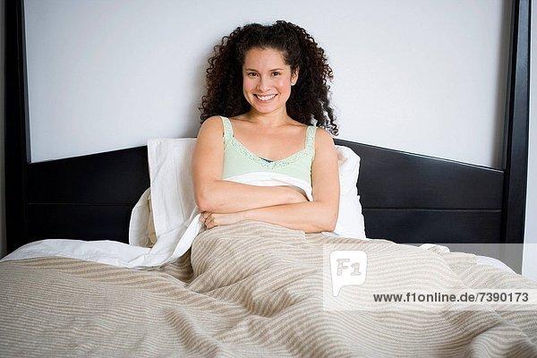 sitzend  überqueren  Frau  lächeln  Bett