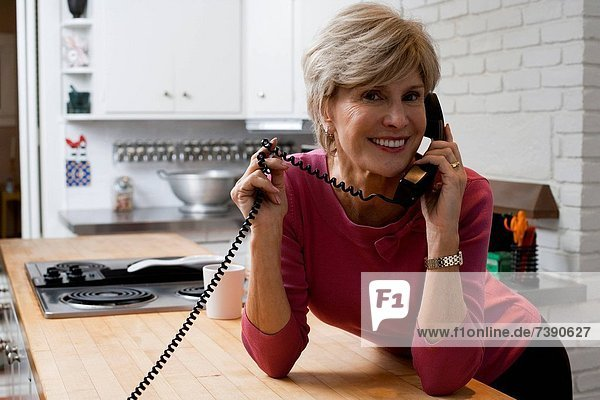 Frau  sprechen  Küche  Telefon  reifer Erwachsene  reife Erwachsene