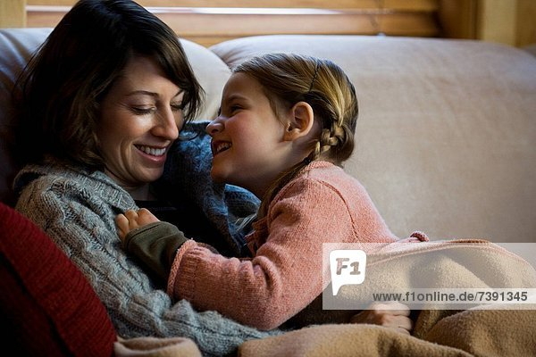 Woman with young girl snuggling on sofa
