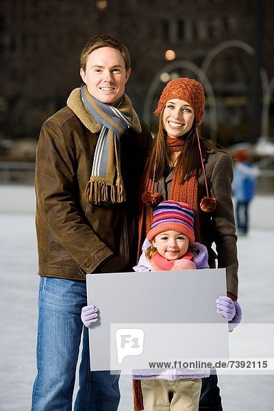 Man and woman with girl holding blank sign outdoors in winter