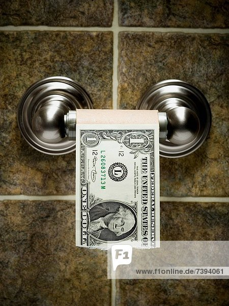 US dollar bills on toilet paper roll