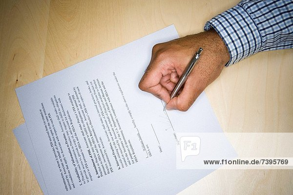 High angle view of a mid adult mans hand writing on paper