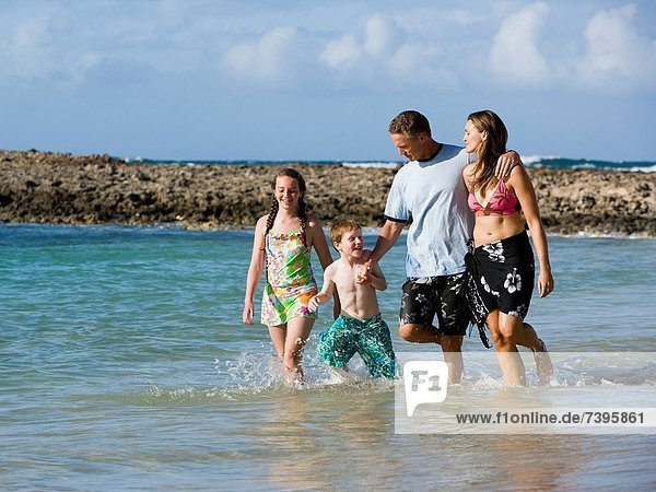Family of four playing in water outdoors laughing