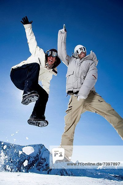 Two friends jumping outside in the snow