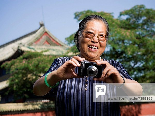 Mature woman with camera outdoors smiling