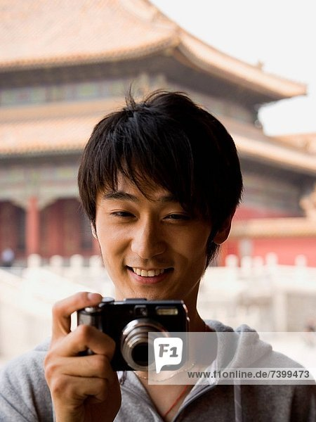 Teenage boy outdoors with digital camera smiling