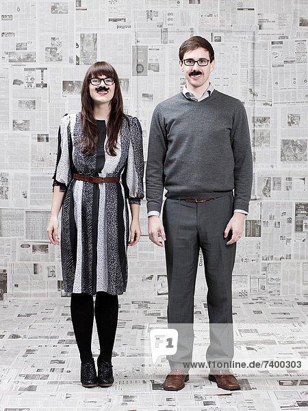 Studioaufnahme  stehend  bedecken  Mensch  zwei Personen  Zeitung  Menschen  Zimmer  Illusion  2  jung