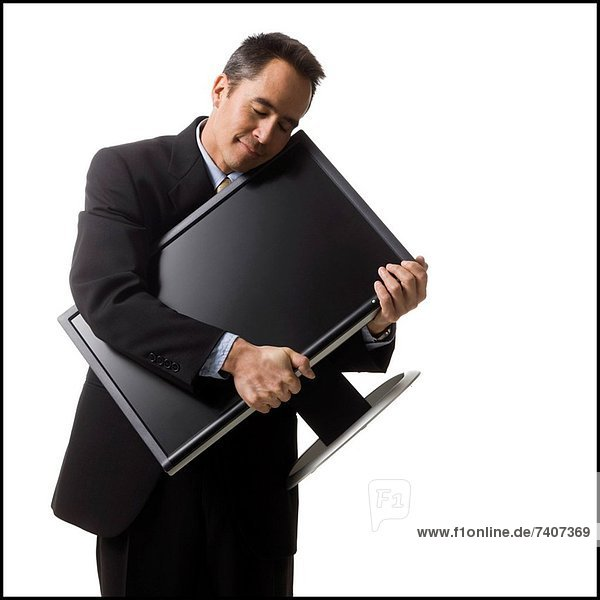 businessman holding a flat screen monitor