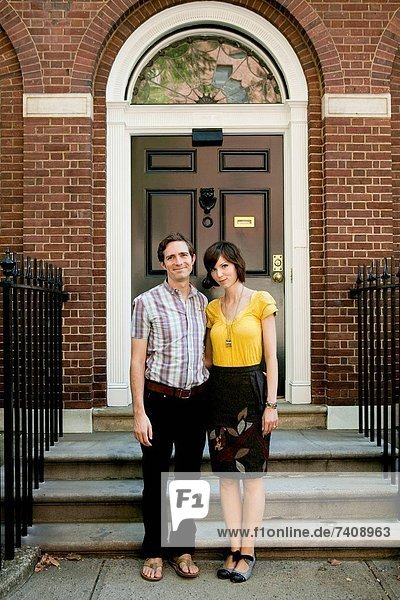 USA  New York  New York City  Portrait of young couple in front of apartment building