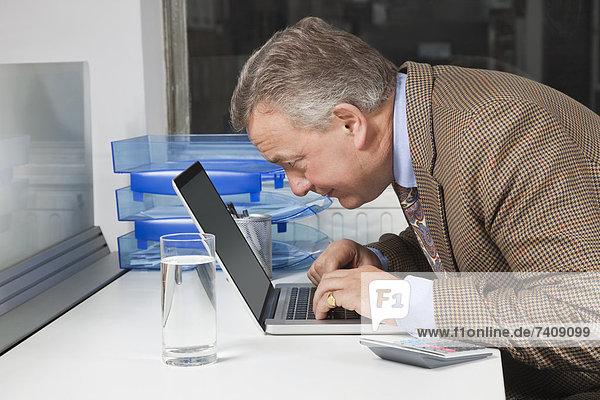 benutzen  Schreibtisch  reifer Erwachsene  reife Erwachsene  Notebook  Geschäftsmann  Büro  Ansicht  Seitenansicht