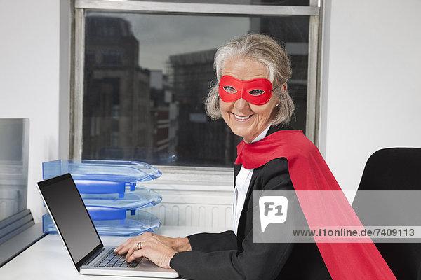Senior  Senioren  benutzen  Portrait  Geschäftsfrau  Schreibtisch  Notebook  Superheld  Büro  Kostüm - Faschingskostüm