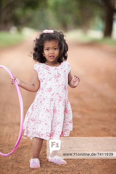 Mädchen spielt mit Hula Hoop auf Schotterpiste