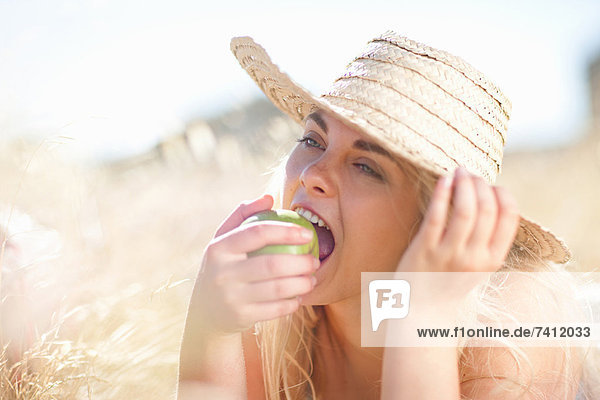 Frau isst Apfel im hohen Gras