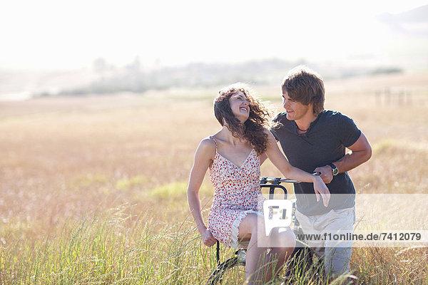 Paar spielt auf dem Fahrrad im hohen Gras