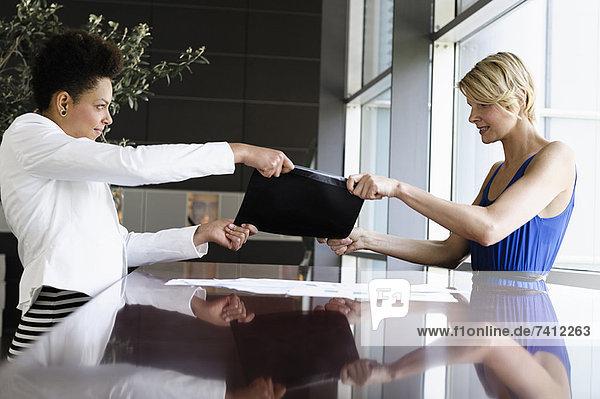 Geschäftsfrauen streiten um Ordner