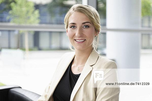 Lächelnde Geschäftsfrau im Stuhl sitzend