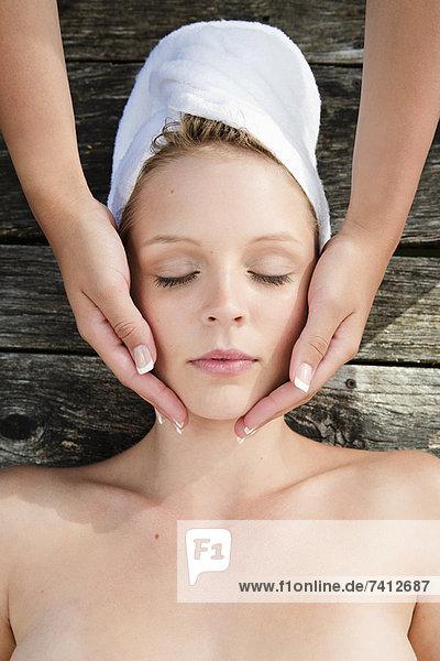 Frau mit Massage auf Holzdeck