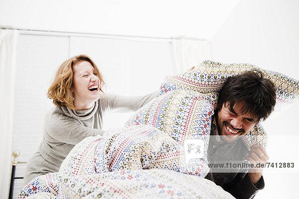 Lächelndes Paar spielt im Bett