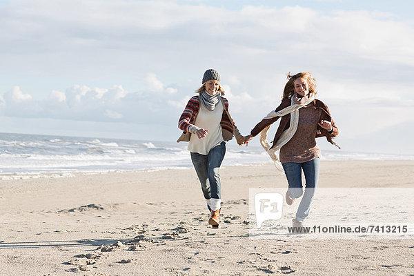 Lächelnde Frauen beim Laufen am Strand