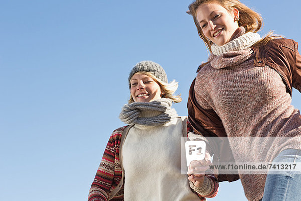 Lächelnde Frauen beim Laufen im Freien