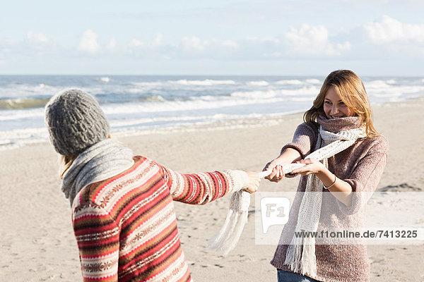 Lächelnde Frauen spielen am Strand