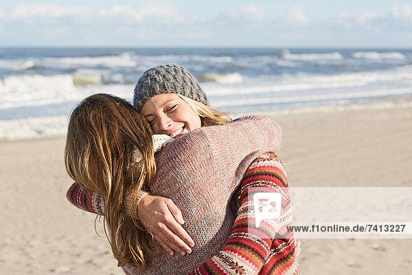 Lächelnde Frauen  die sich am Strand umarmen